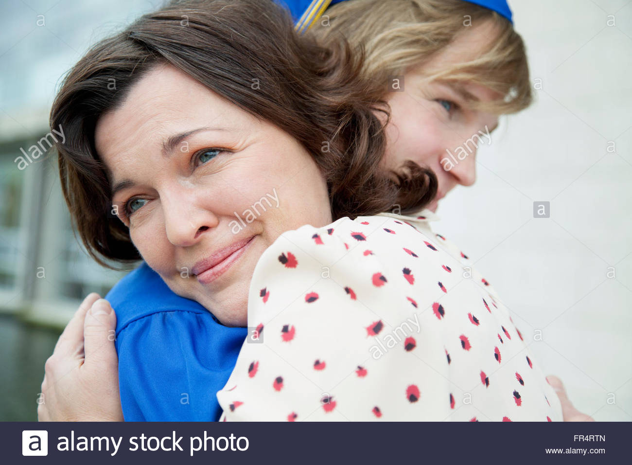 mom hugging her graduate son - Stock Image