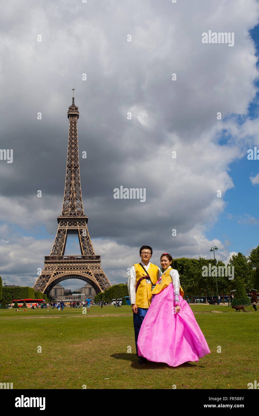 Asian couple with traditional cloths posing for selfy in front of Eifel tower in Paris, France - Stock Image