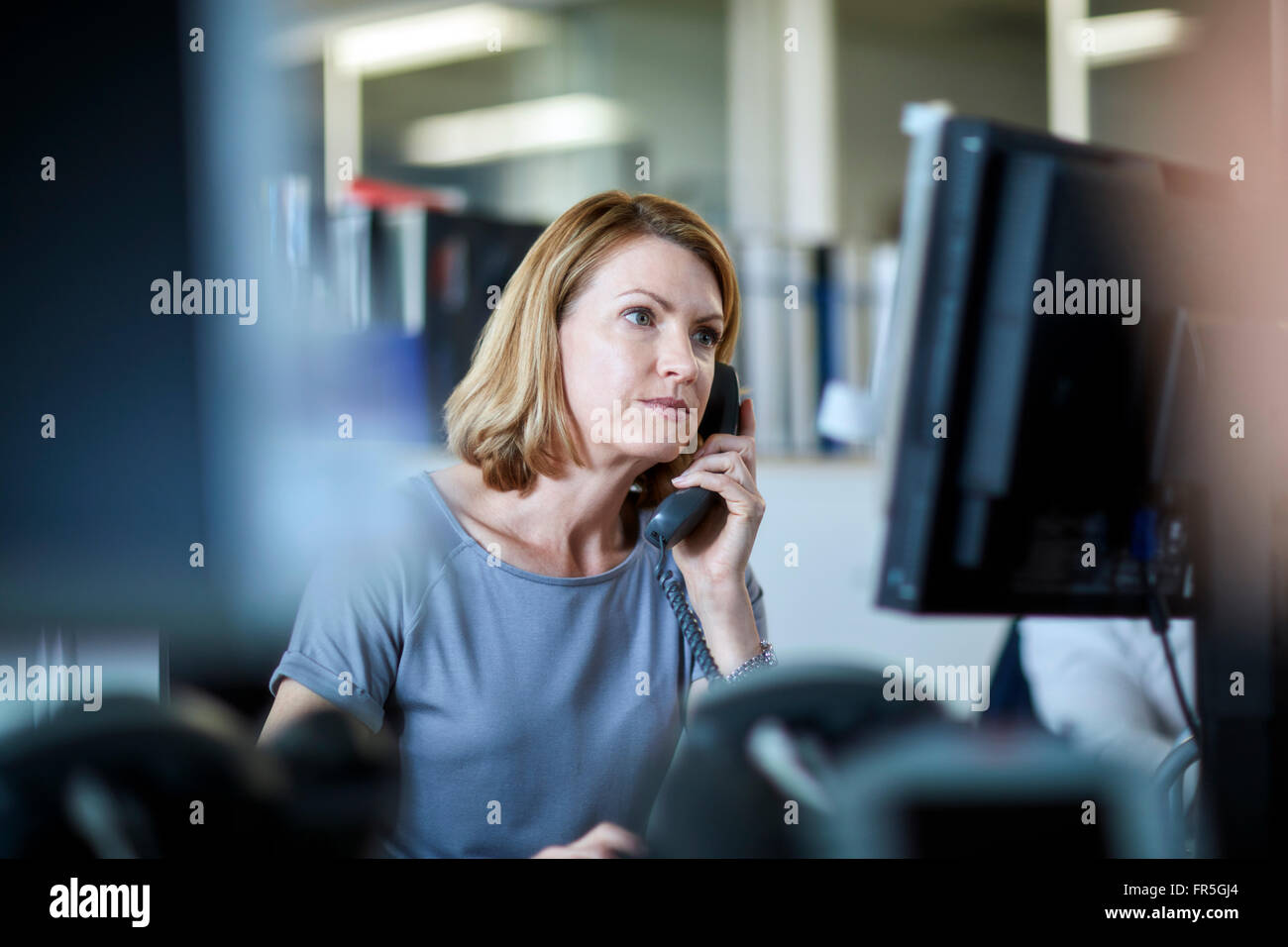 Businesswoman talking on telephone and working at computer - Stock Image