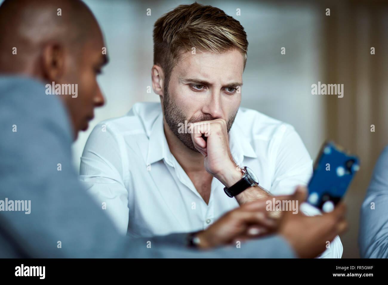 Serious businessmen examining part - Stock Image