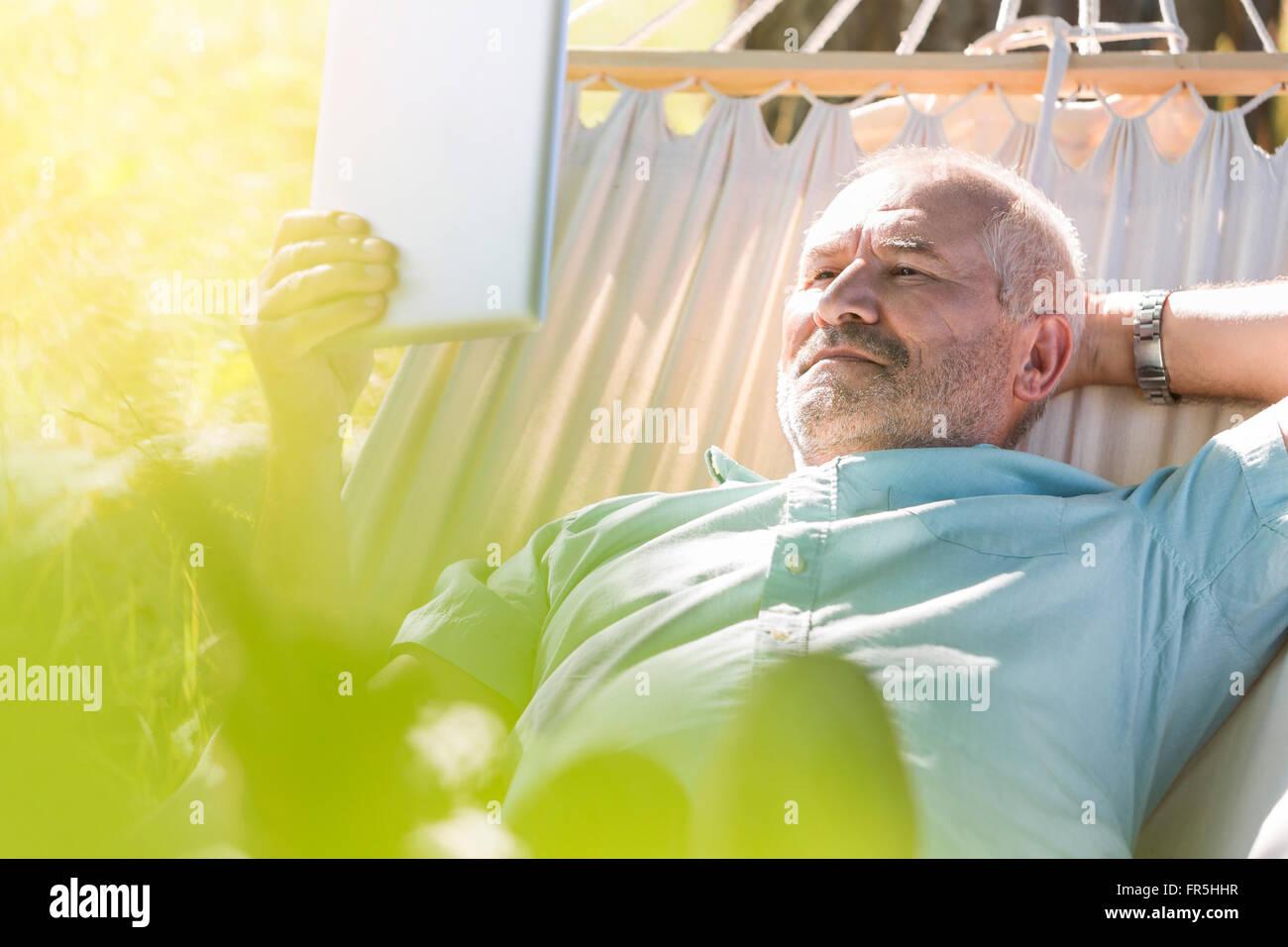 Senior man using digital tablet and relaxing in summer hammock - Stock Image
