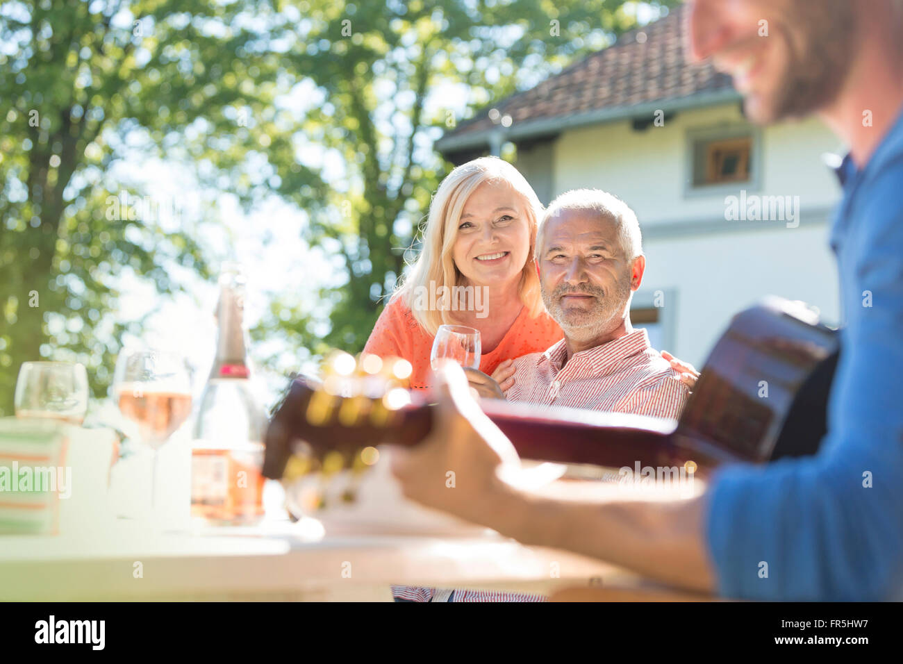 Senior couple drinking wine and watching adult son playing guitar on sunny patio - Stock Image