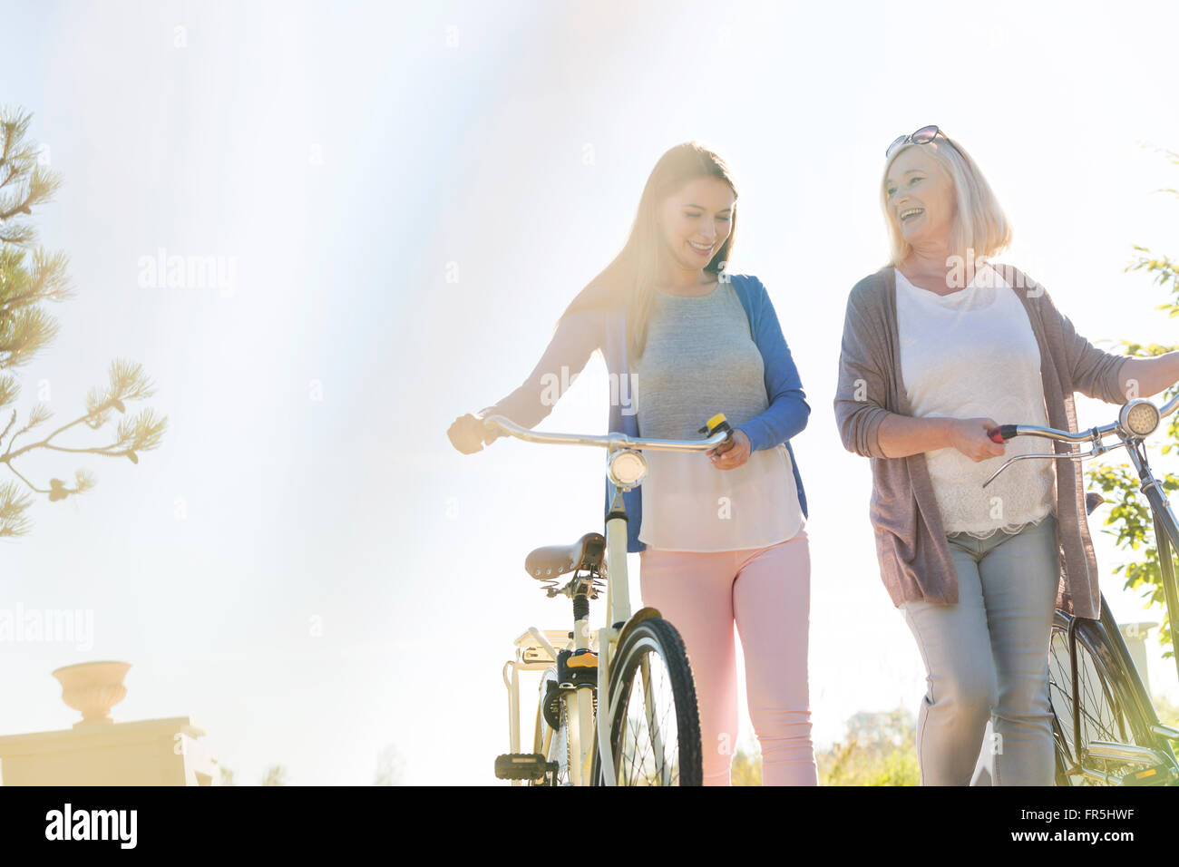 Mother and adult daughter walking bicycles - Stock Image