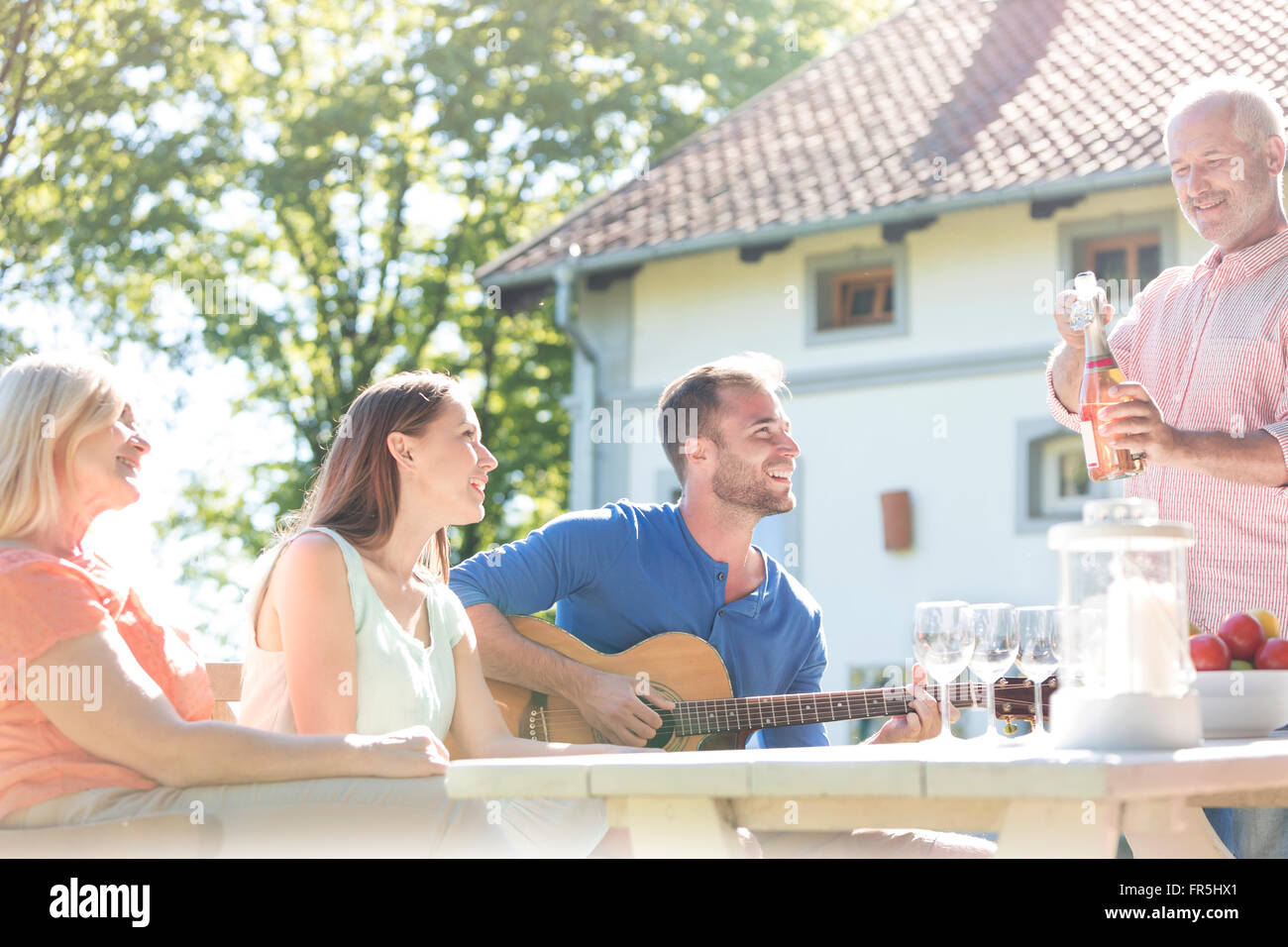 Father opening bottle of rose wine for family at sunny patio table - Stock Image