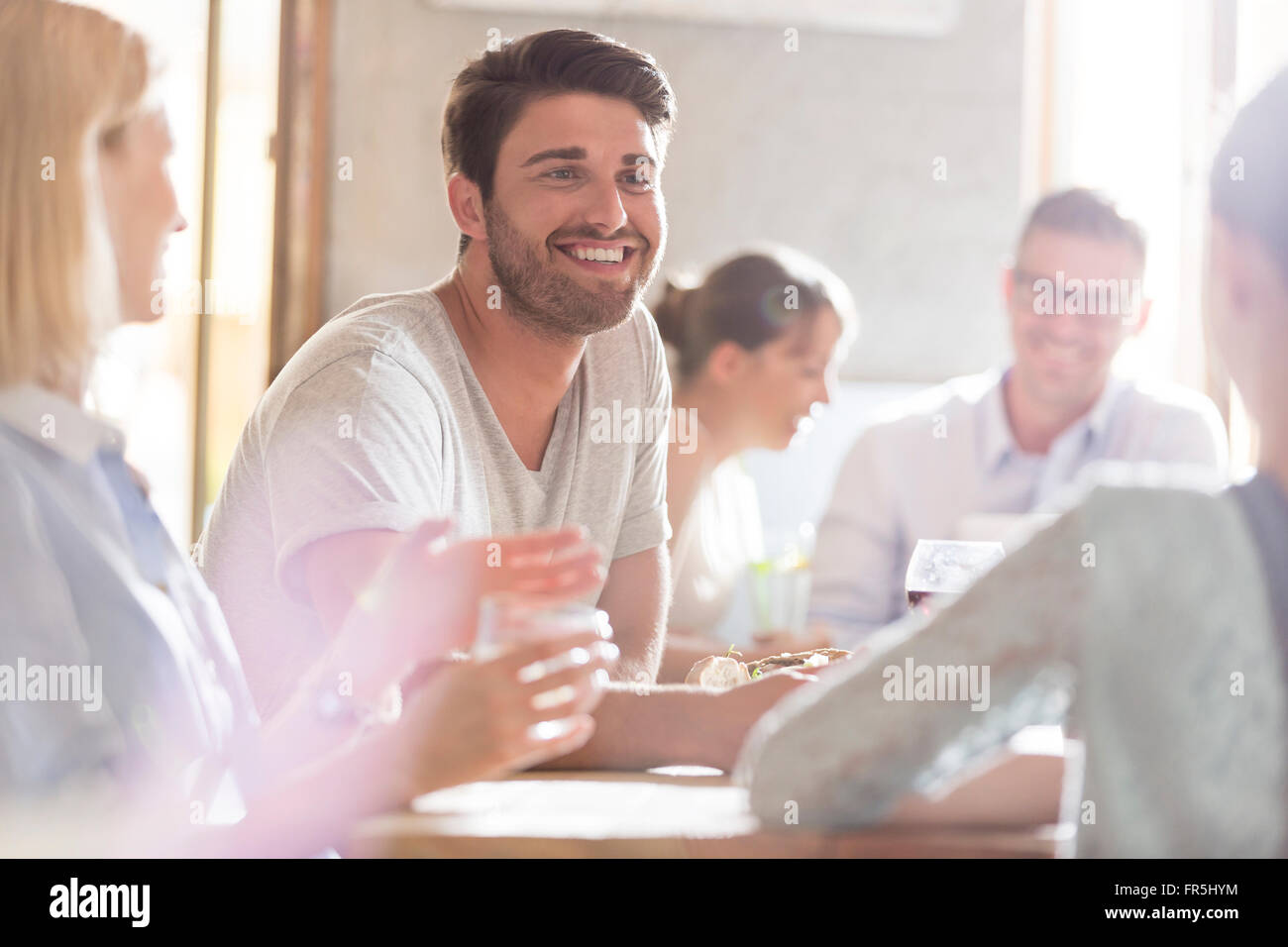 Smiling man with friends at cafe - Stock Image