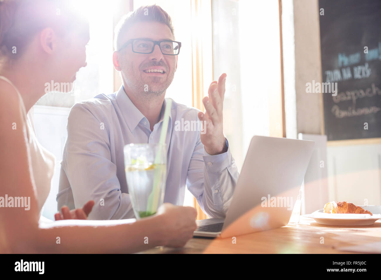 Business people with laptop talking in sunny cafe - Stock Image