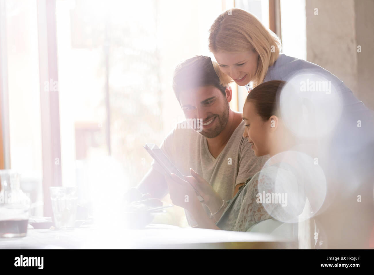Family using digital tablet in sunny cafe - Stock Image