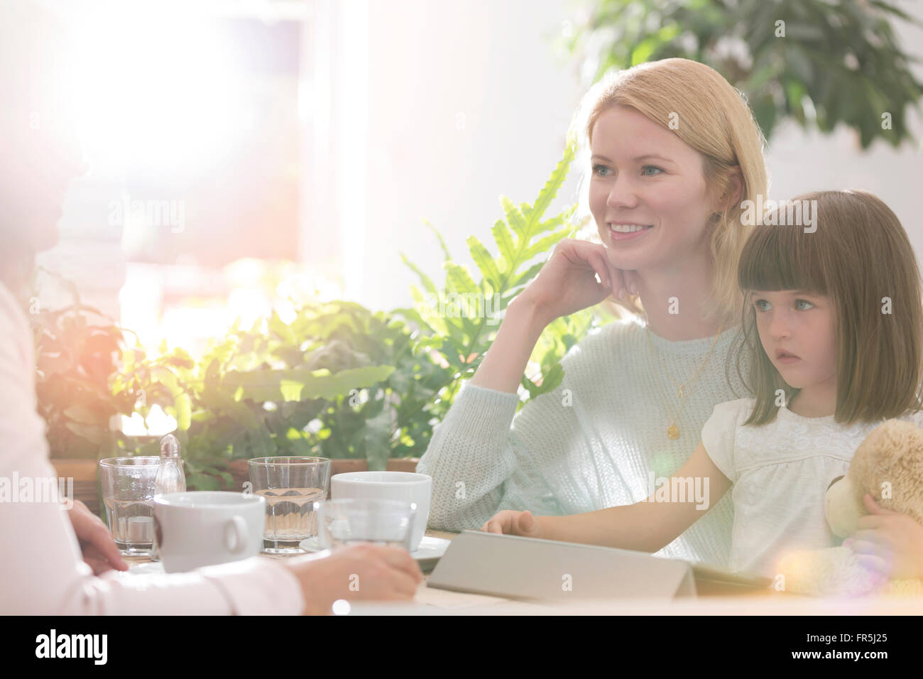 Family at cafe table - Stock Image