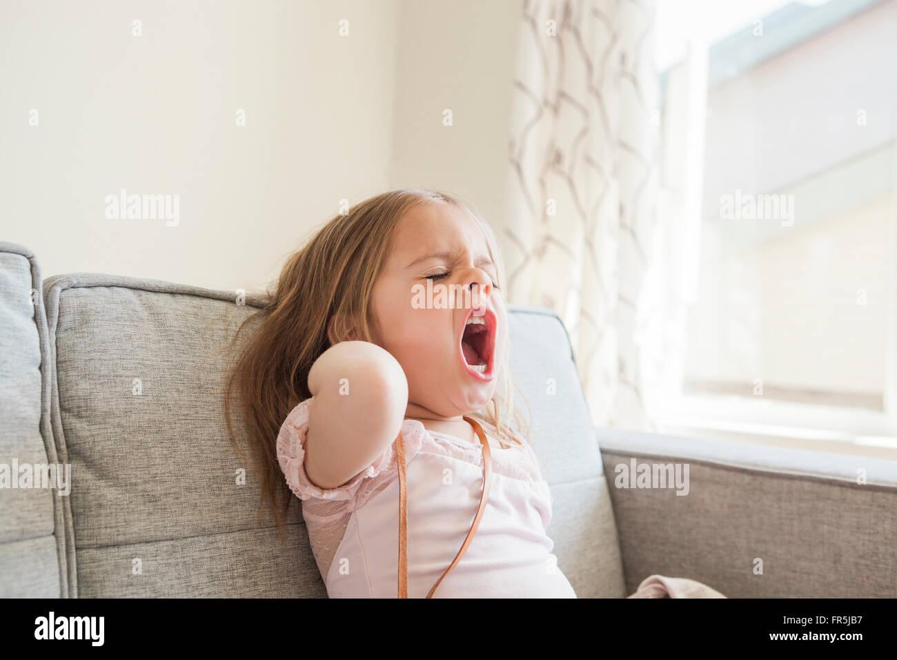 Toddler girl yawning on sofa - Stock Image