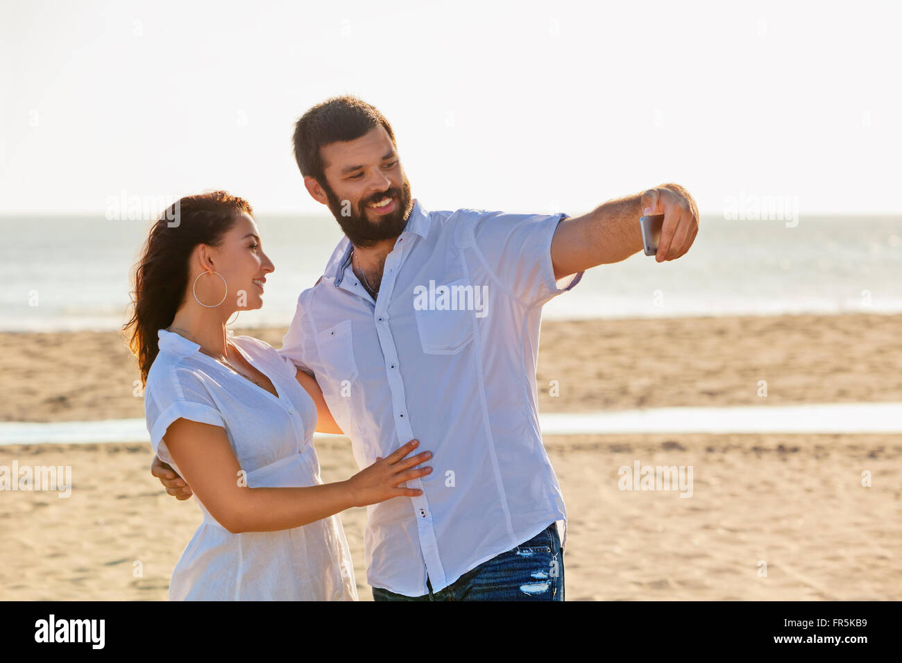 Happy family on honeymoon holidays - just married loving couple have fun and taking selfie for social network on - Stock Image