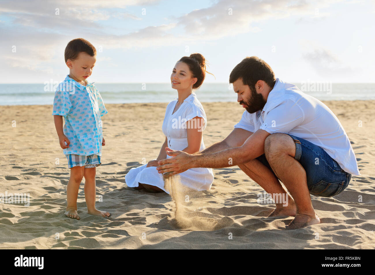 Happy family - mother, father and small baby son sit on sunset sea beach and play with sand slipping through man - Stock Image