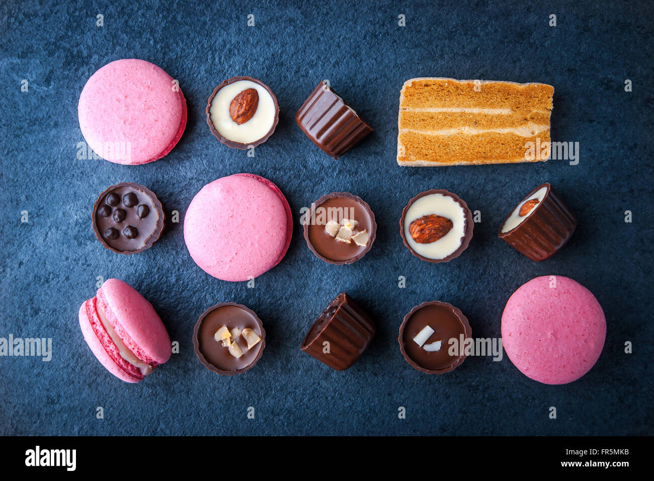 Composition from chocolates and pink macaroon horizontal, super still life - Stock Image