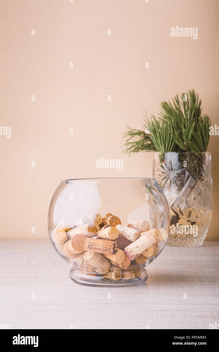 Vase with corks and coniferous branch on the table vertical - Stock Image