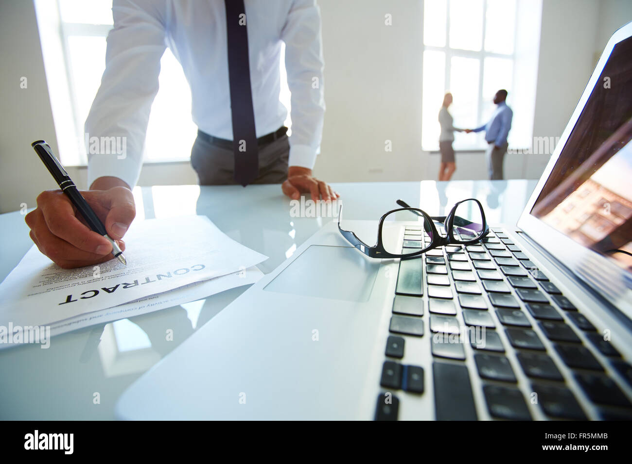 Close-up of a businessman holding pen and signing papers - Stock Image