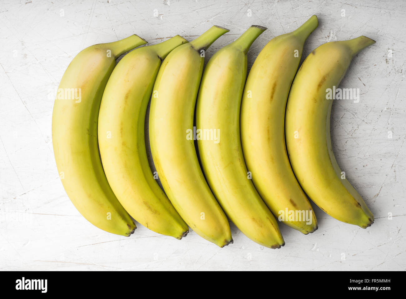 Yellow bananas are laid out in a rectangle horizontal - Stock Image