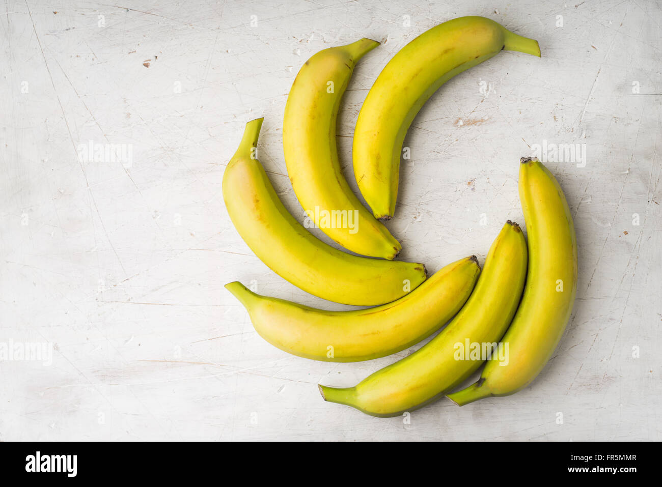 Yellow bananas are laid by a fan on a white table horizontal - Stock Image