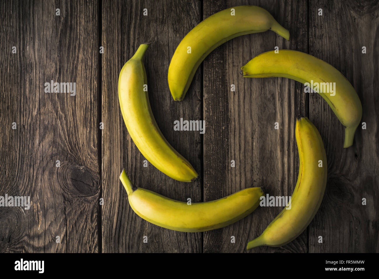 Green bananas on an old wooden table horizontal - Stock Image