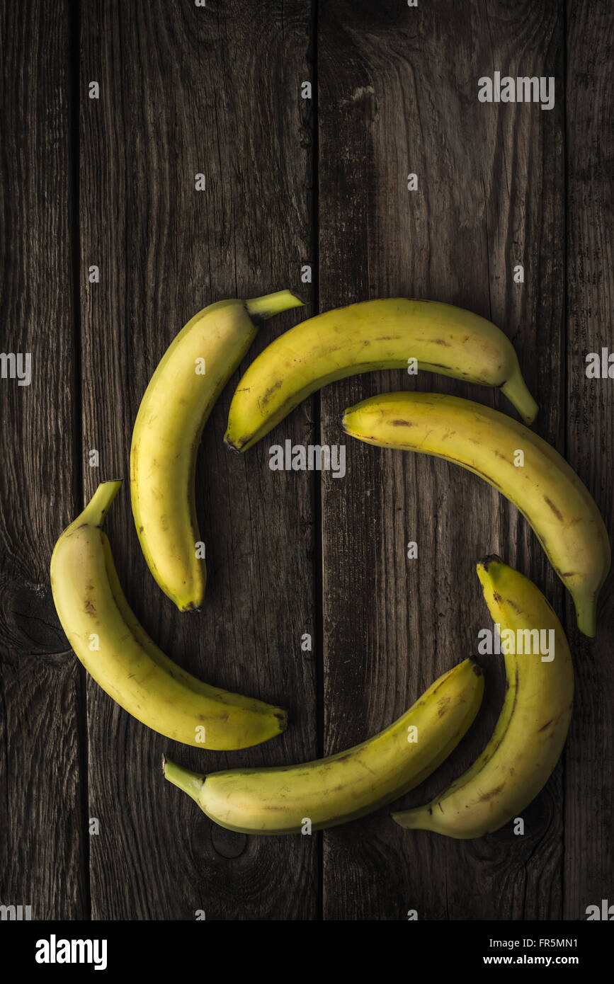 Yellow bananas on old wooden boards vertical - Stock Image