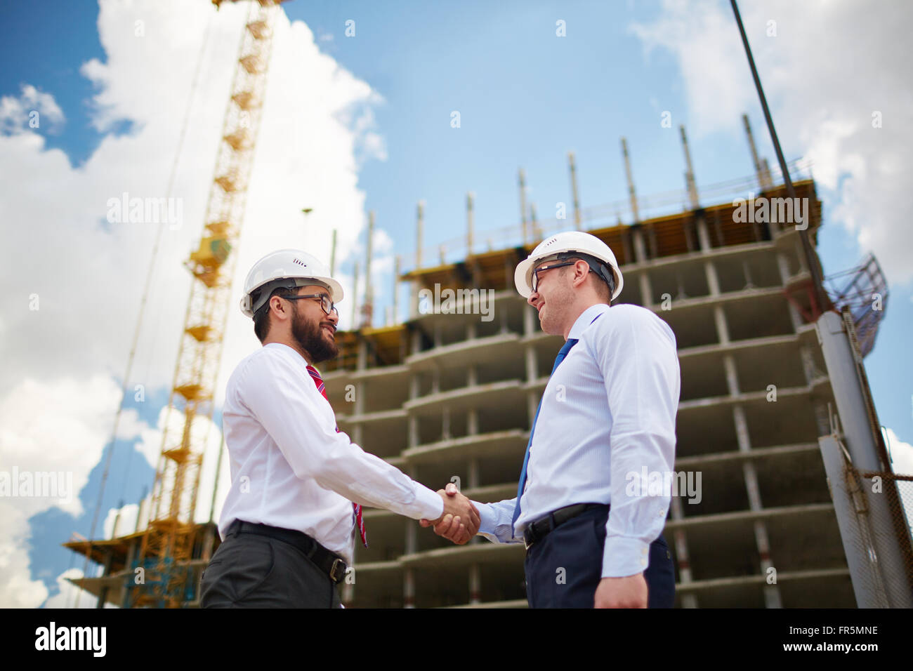 Two young architects in hardhats greeting each other with handshake - Stock Image