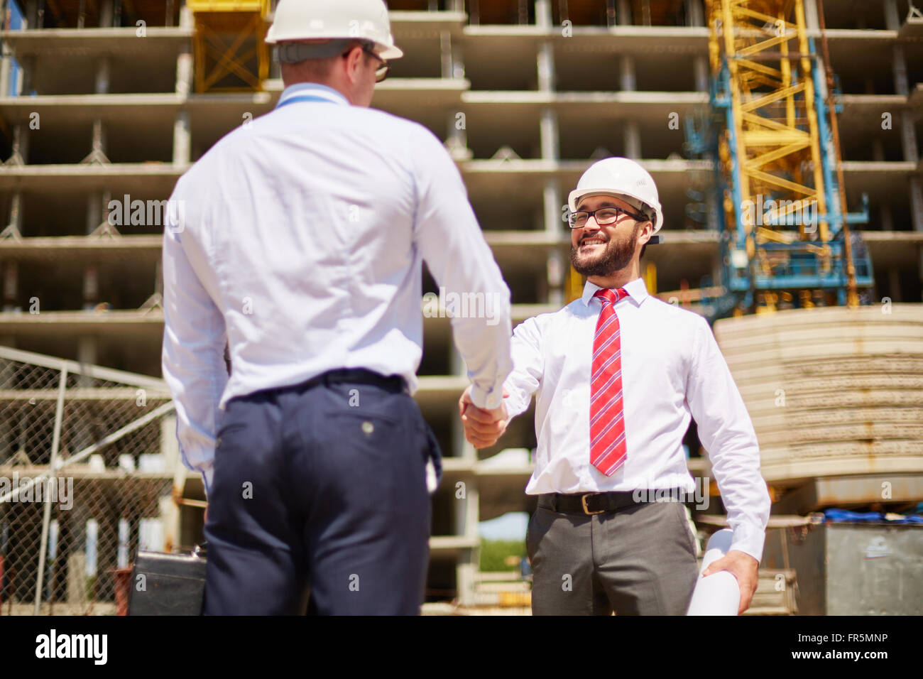 Young businessmen in hard hats shaking hands - Stock Image