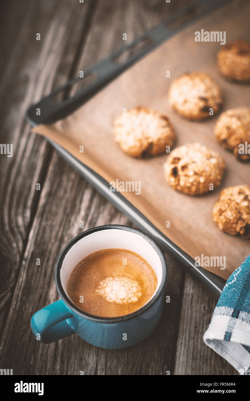 Oatmeal cookies and coffee cup on a wooden table vertical - Stock Image