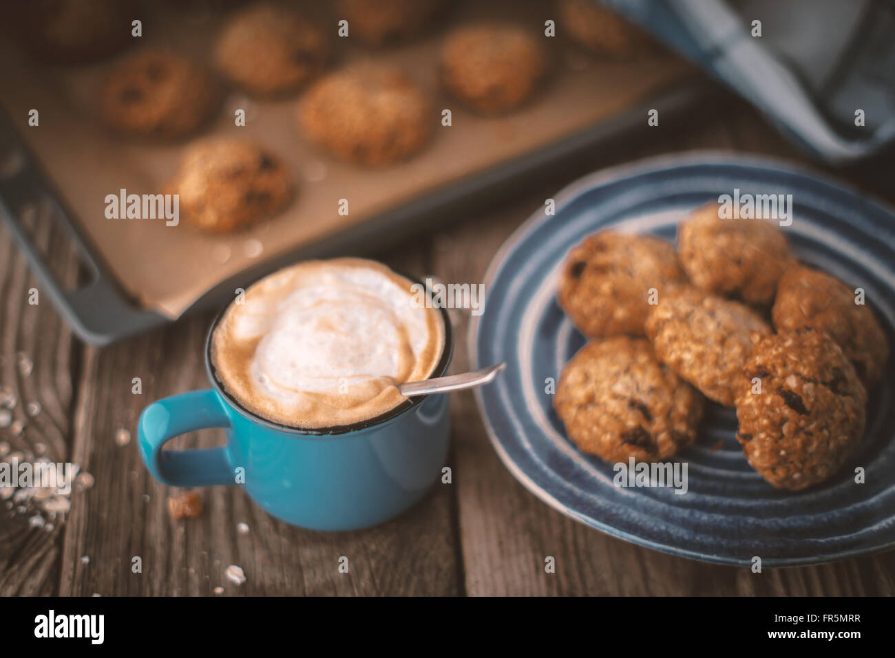 Baking tray and a plate of oatmeal cookies on the wooden table horizontal - Stock Image