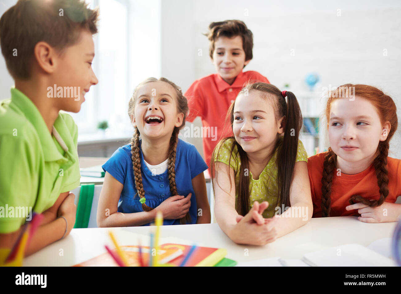 Elementary students talking together at the table - Stock Image