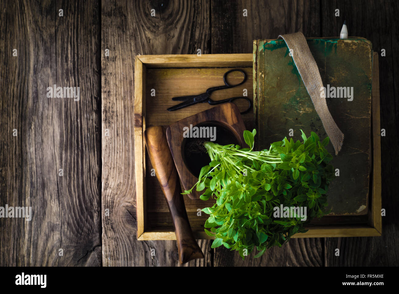 Basil, a book and a mortar on a wooden table horizontal Stock Photo