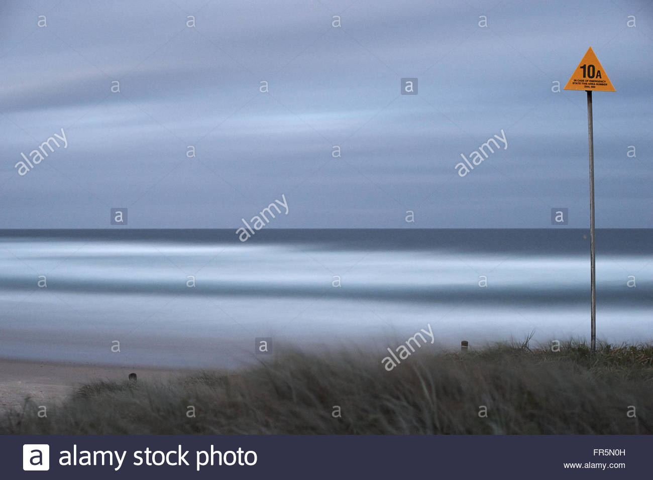 A long-exposure image of the Pacific Ocean - a yellow triangular emergency marker starkly contrasting the serenity; - Stock Image