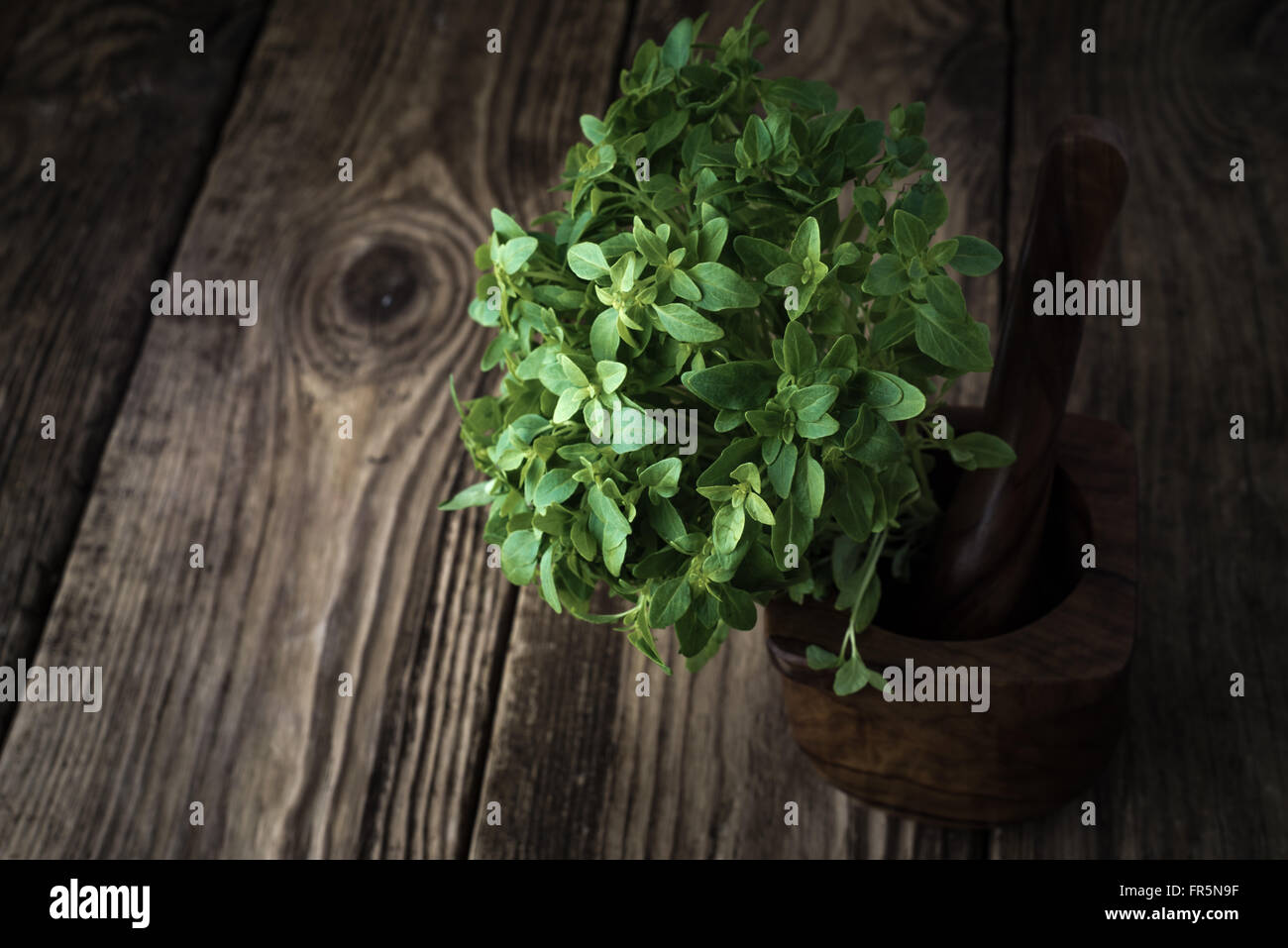 Basil and mortar on old boards horizontal - Stock Image