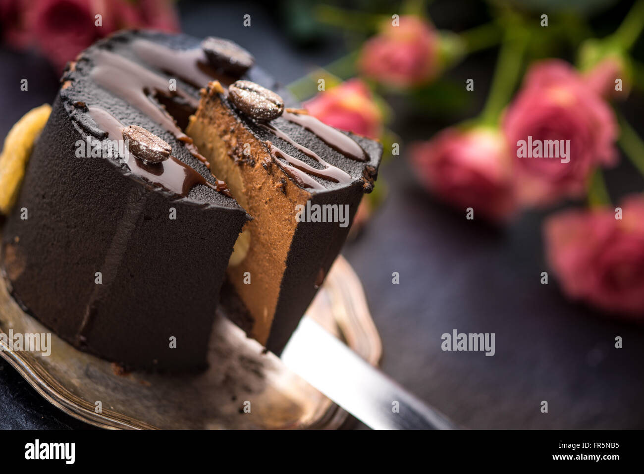 Coffee mousse and a bouquet of roses on a blue table horizontal - Stock Image