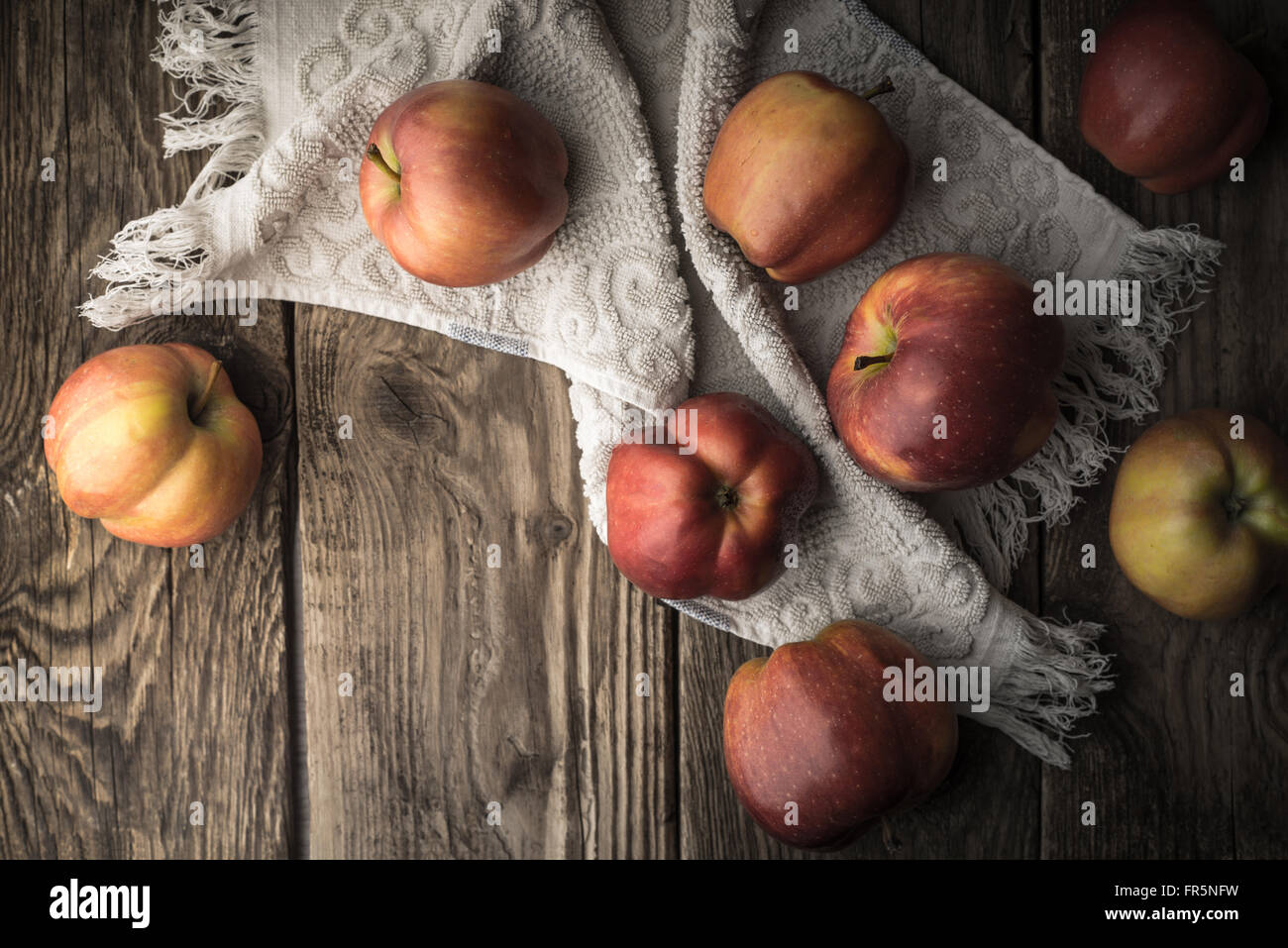 Red apples and towel on the old boards horizontal - Stock Image