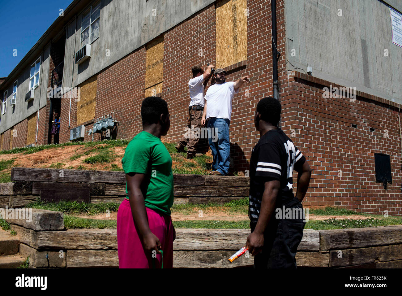 Memphis, TN, USA. 25th Apr, 2015. Workers board up windows at the Warren apartments as residents begin to move their - Stock Image