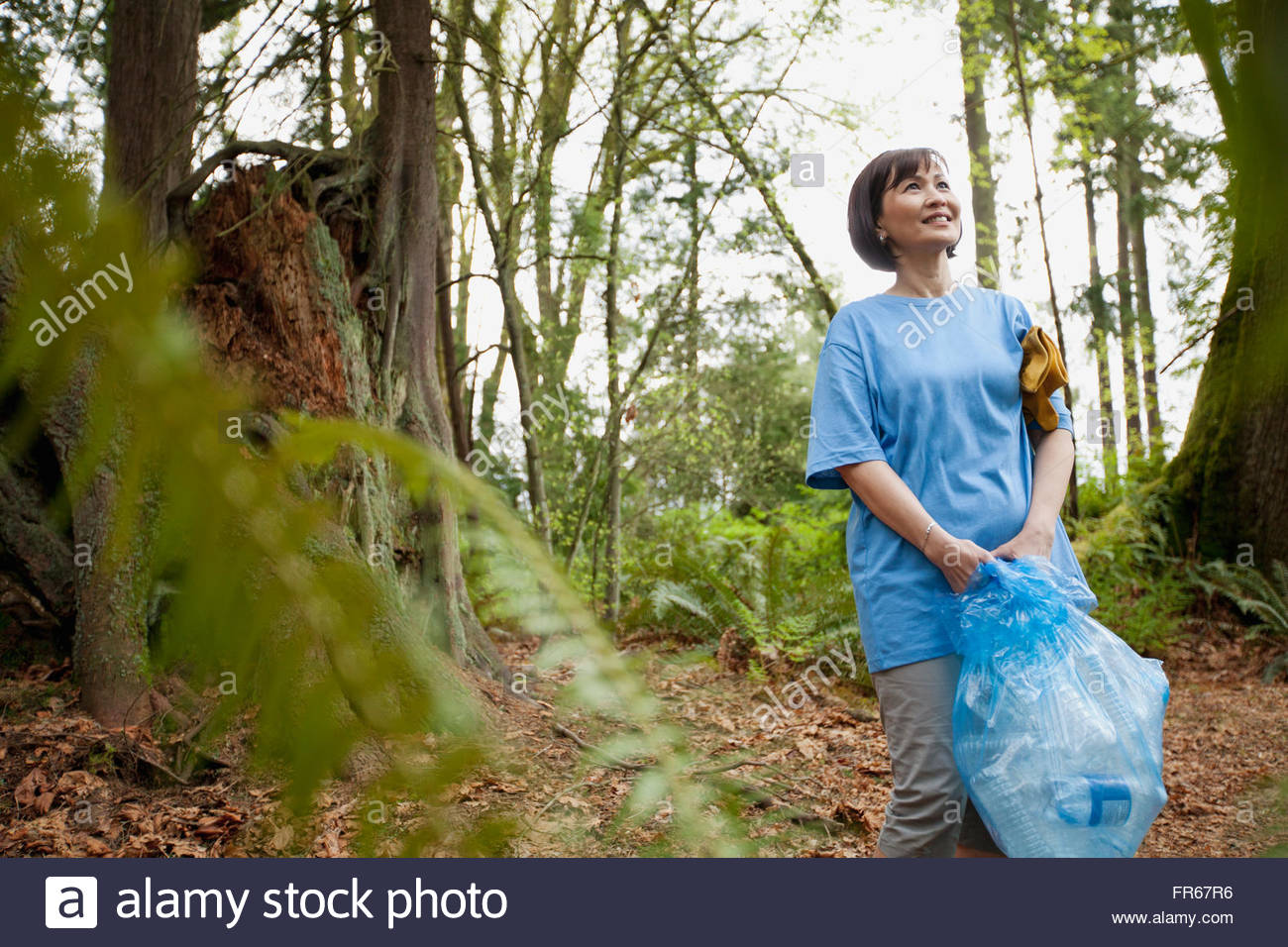 mature woman helping to clean up park - Stock Image