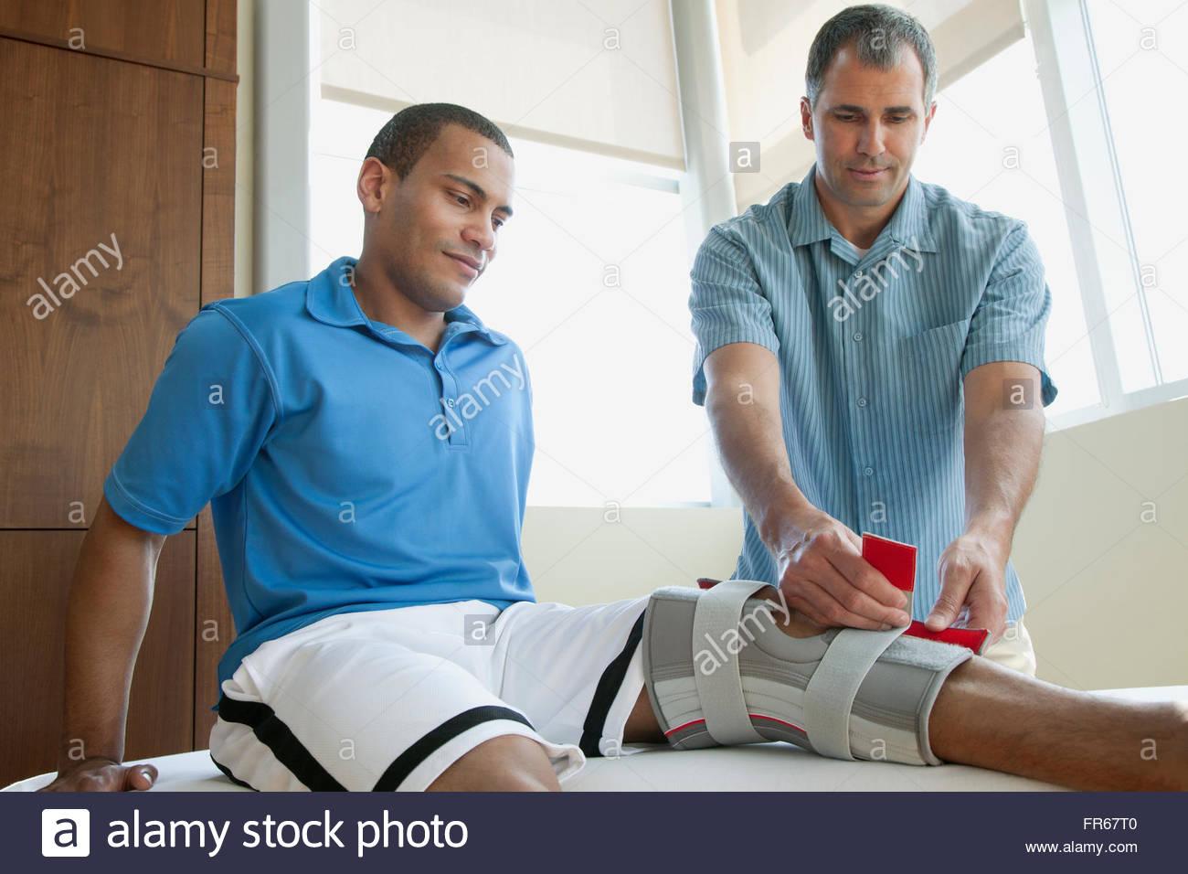 doctor applying brace to patients knee - Stock Image