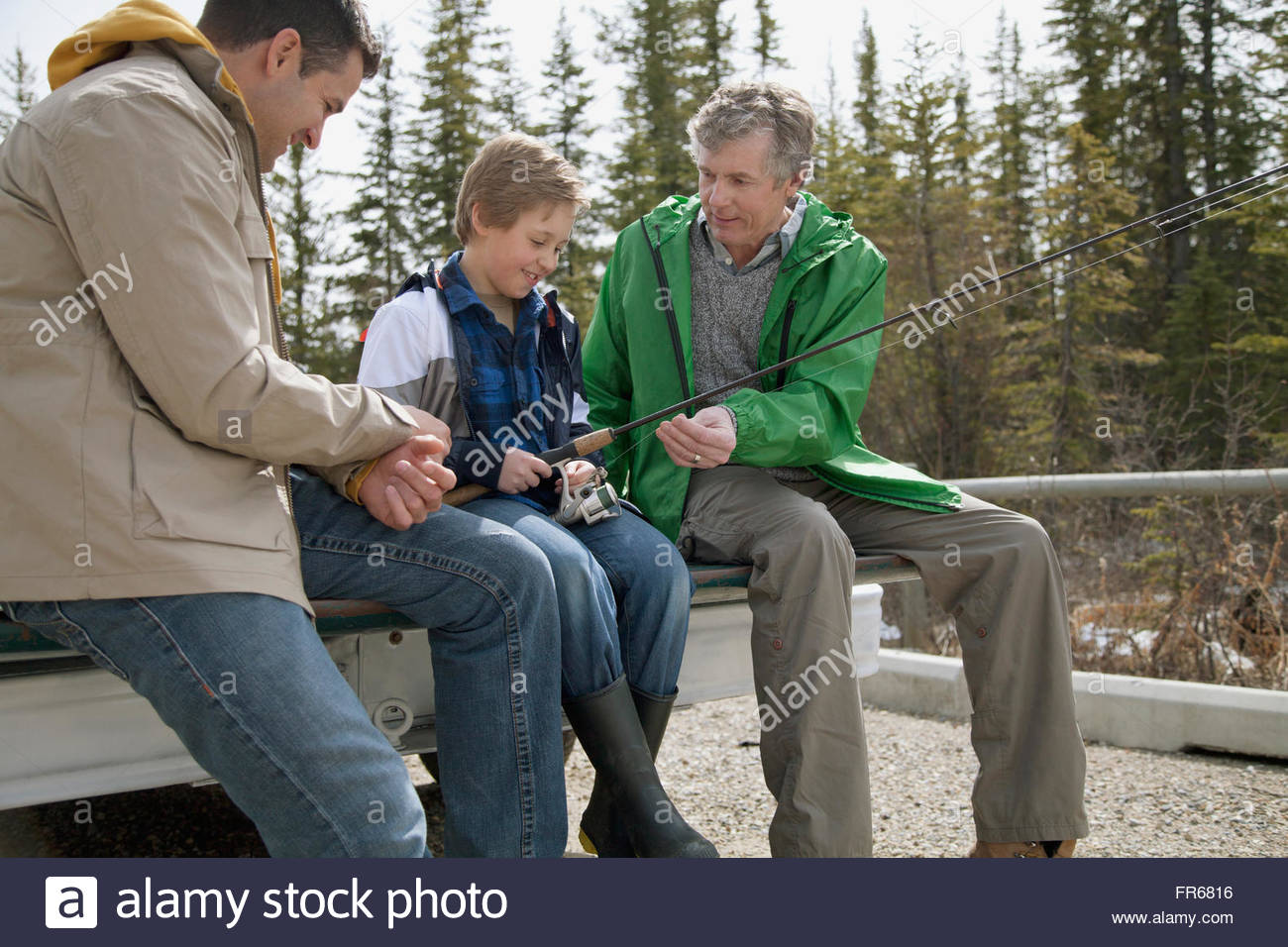 three generations of men prepping for fishing - Stock Image