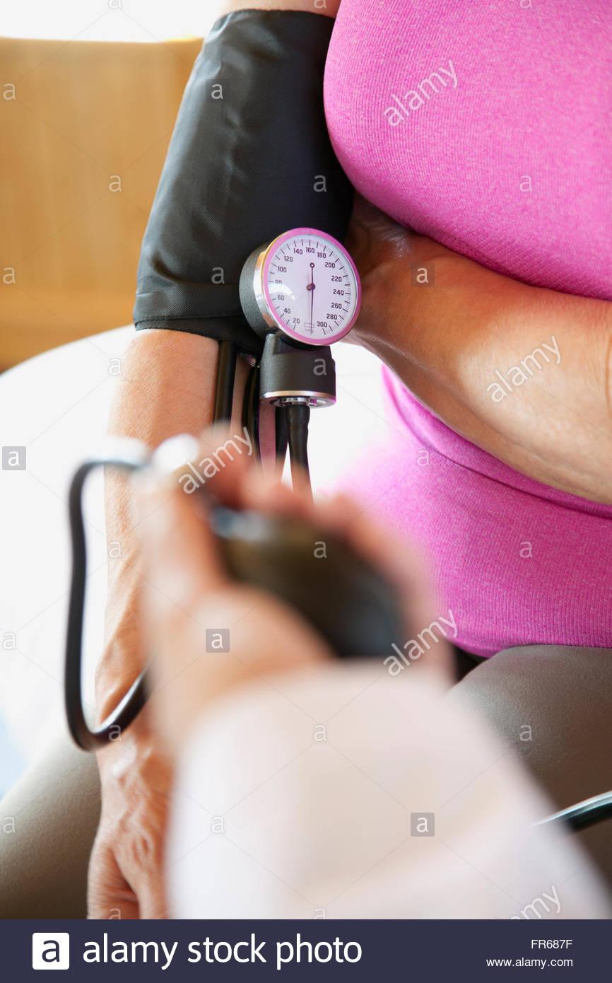 senior having blood pressure taken - Stock Image