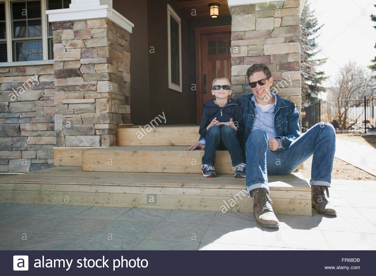 dad and son sitting on front stairs of residence - Stock Image