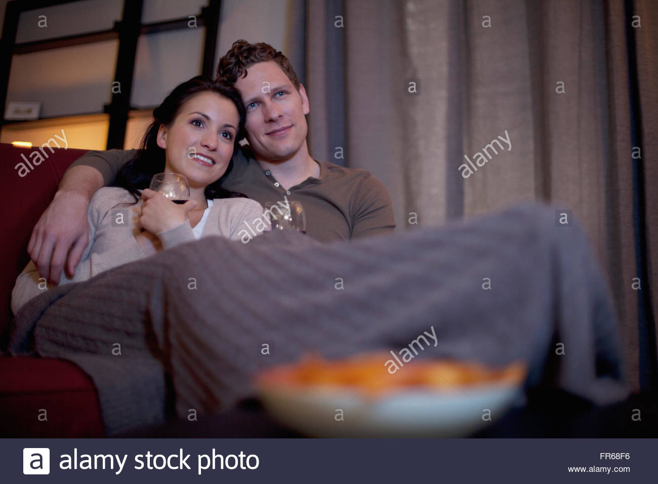 couple cuddling on the couch - Stock Image