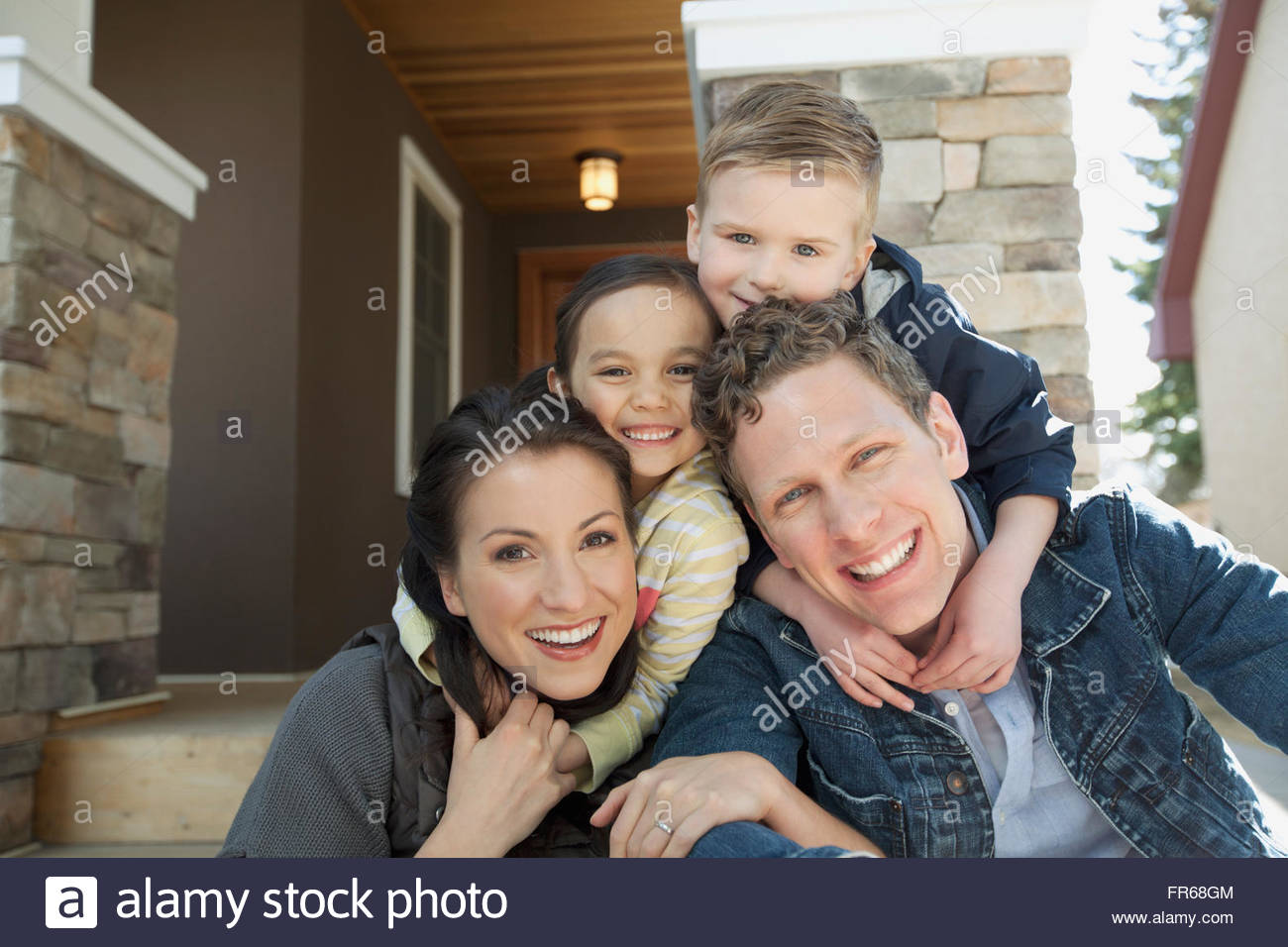 portrait of young family outside residence - Stock Image