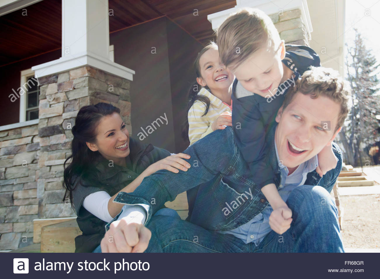 young family playing outside on the front porch - Stock Image