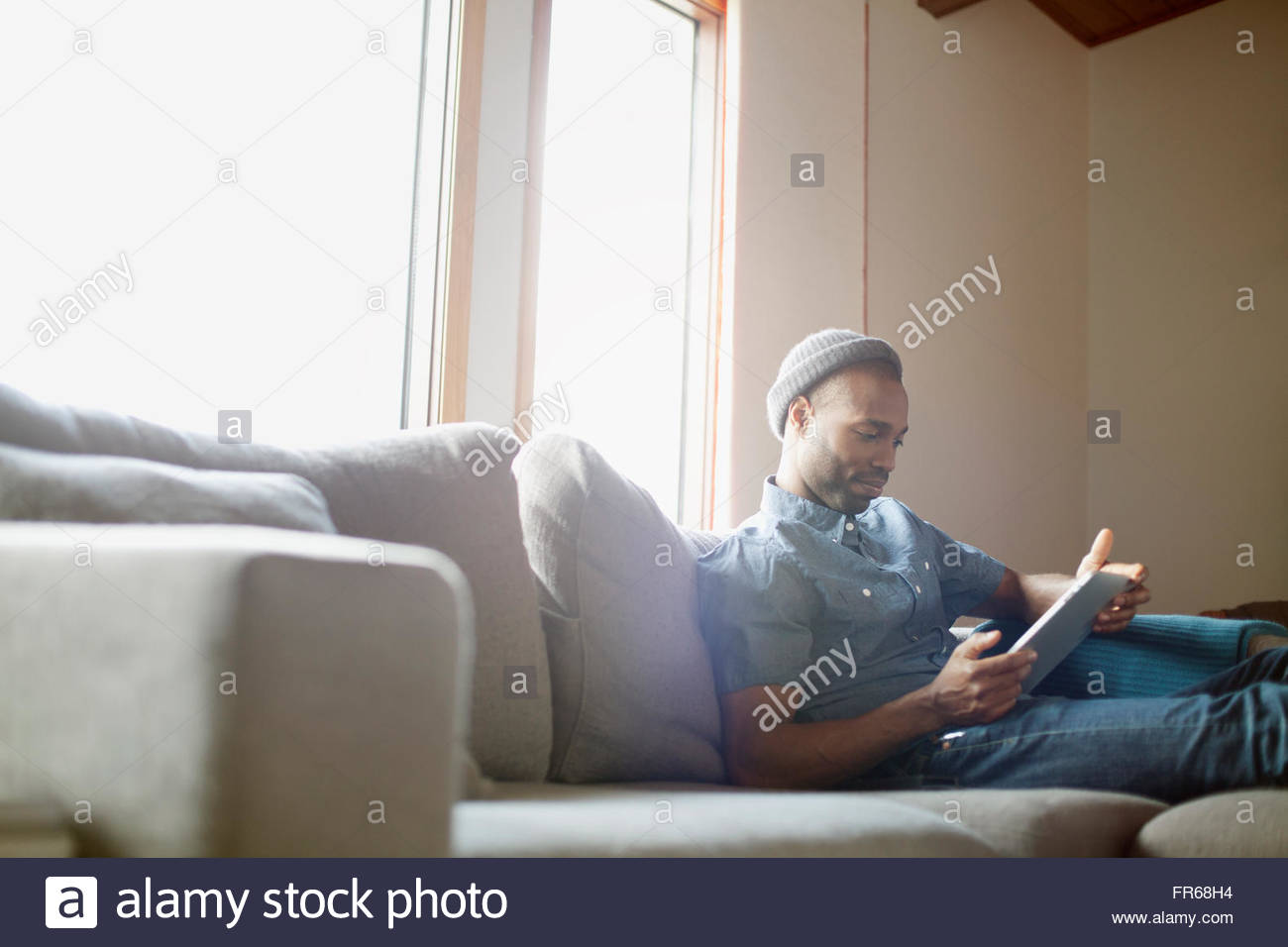man relaxing on soda with ipad - Stock Image