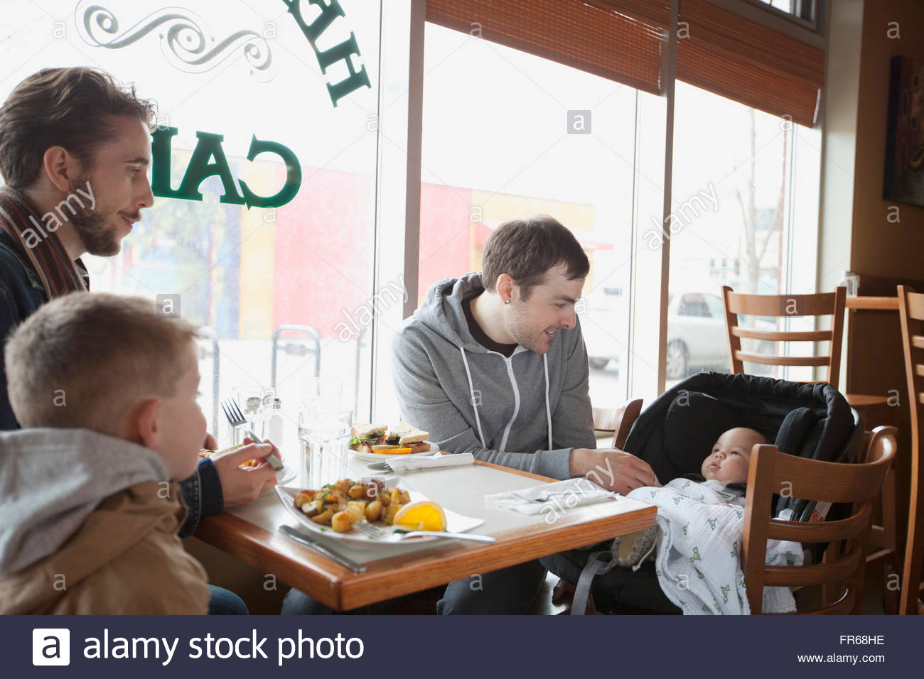 fathers enjoying lunch with young sons - Stock Image