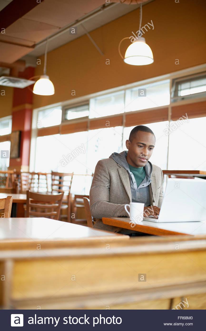 man using wi-fi technology at cafe - Stock Image