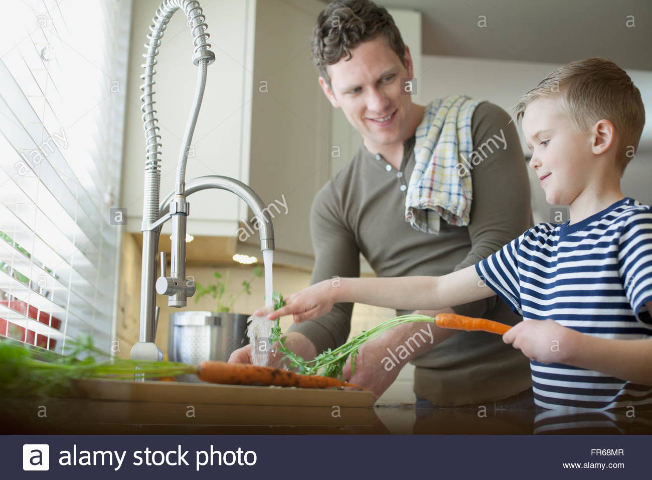dad and young son washing carrots in kitchen - Stock Image