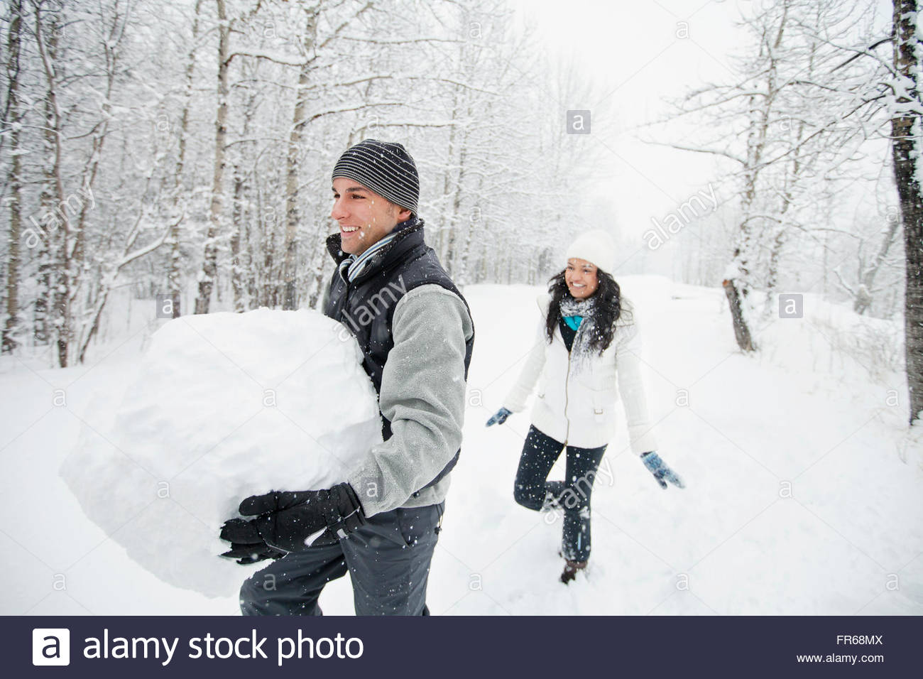 friends creating a snowman - Stock Image
