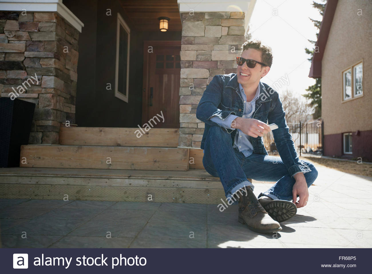 attractive man sitting on front steps of residence - Stock Image
