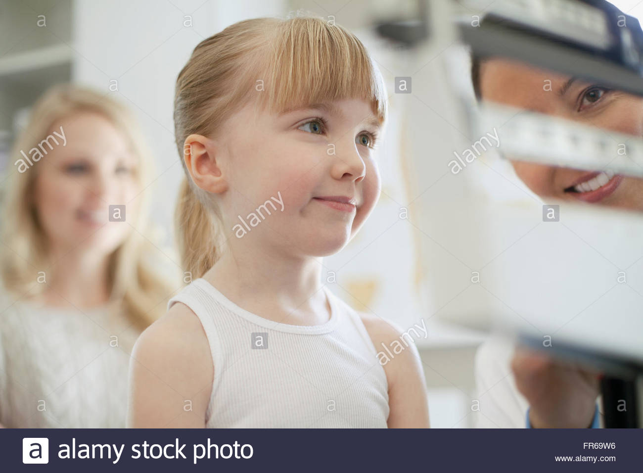 mother with daughter at doctors appointment - Stock Image