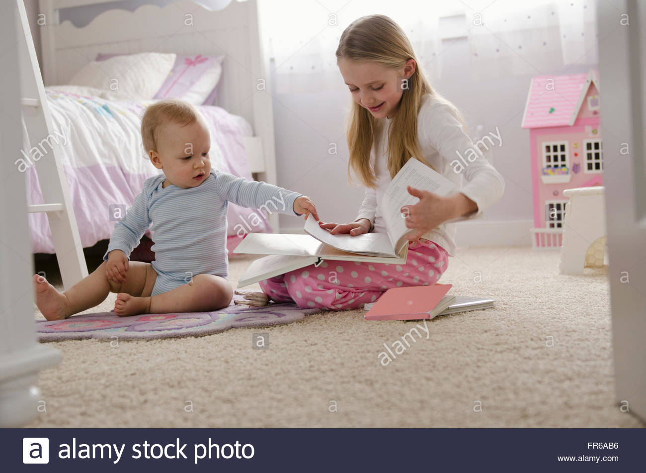 sister reading with younger brother in bedroom - Stock Image