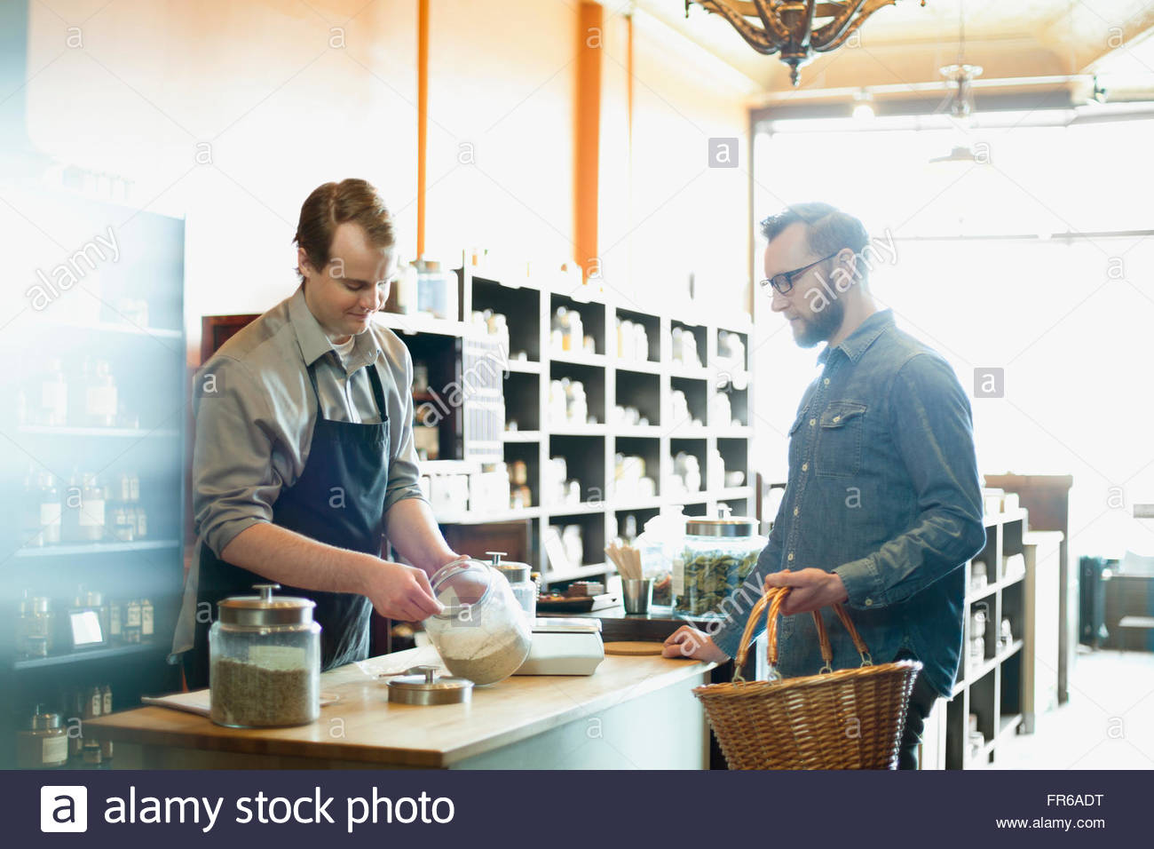 merchant measuring product at retail spice store - Stock Image